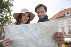 Happy tourist couple reading map outdoors Stock Image