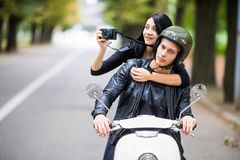 Happy tourist young couple on scooter ride in new city. Woman making photo on camera while riding outdoors royalty free stock photos
