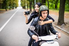 Happy tourist young couple on scooter ride in new city. Woman making photo on camera while riding outdoors royalty free stock photo