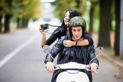Happy tourist young couple on scooter ride in new city. Woman making photo on camera while riding outdoors royalty free stock photography
