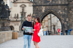 Happy tourist couple traveling on Charles Bridge in Prague at famous places with city map. Happy tourist couple, men and women traveling on holidays in Europe stock images