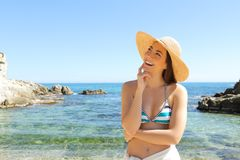 Happy tourist dreaming looking at side on vacation on the beach stock image