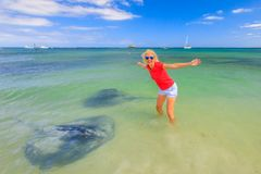 Happy tourist with Eagle Ray. Happy blonde woman with open arms near two big Australian Eagle Ray close to shore in Hamelin Bay, Western Australia. Female Royalty Free Stock Image