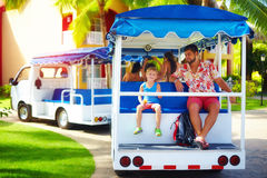 Happy tourist family enjoying vacation while riding in vehicle through the hotel area. Transportation service. Happy tourist family, father and son enjoying Royalty Free Stock Image
