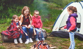 Happy tourist family on journey hike. mother and children fry sa. Happy tourist family on a journey hike. mother and children fry sausages on bonfire near the Stock Photos