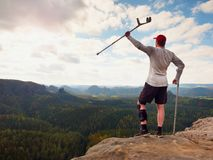 Happy tourist with forearm crutch above head achieved mountain peak. Hiker with broken knee in immobilizer. Happy tourist with forearm crutch above head achieved Royalty Free Stock Photo