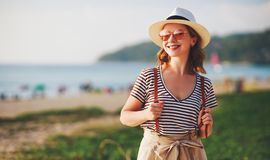 Happy tourist girl with backpack and hat on sea beach stock photos