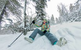 Happy tourist girl with a backpack sits in a winter mauntains trees Stock Photography
