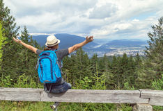 Happy tourist girl with raising hands and backpack sitting in the Austrian Alps mountain and enjoying summer and nature. Stock Images