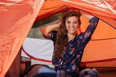 Happy tourist girl smile stretching at tent. In forest royalty free stock images