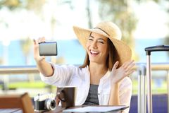 Tourist having a video call on destination. Happy tourist having a video call with a smart phone on travel destination in the beach Royalty Free Stock Photo