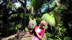 Woman with Coco de Mer coconut. Happy tourist holding Coco de Mer at Fond Ferdinand Nature Reserve, near Anse Marie-Louise, Praslin, Seychelles. Woman with a stock video footage