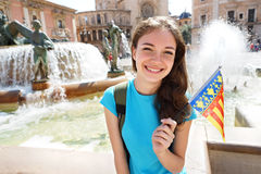 Happy tourist holding flag of Valencian Community. Young girl student exchange for learning the language. Valencia, Spain. Travel and tourism concept Stock Photography
