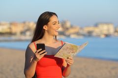 Happy tourist holding map and phone contemplating the beach royalty free stock photos