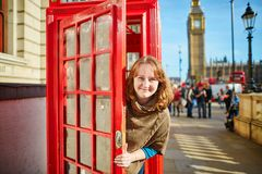 Happy tourist looking out of the red phonebox Stock Photography