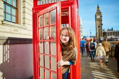 Happy tourist looking out of the red phonebox Royalty Free Stock Photos