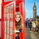 Happy tourist looking out of the red phonebox Royalty Free Stock Photography