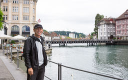 Happy tourist in Lucerne, Switzerland. Smiling happy tourist in Lucerne, Switzerland with Reuss River and the city behind Royalty Free Stock Images