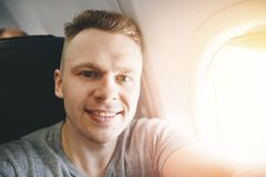 Happy tourist man makes selfie photo in cabin aircraft airplane before departure. Travel concept stock images