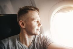 Happy tourist man makes selfie photo in cabin aircraft airplane before departure. Travel concept royalty free stock image