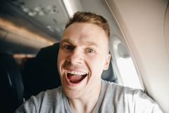 Happy tourist man makes selfie photo in cabin aircraft airplane before departure. Travel concept royalty free stock photography