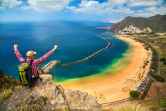 Happy tourist man near Playa de Las Teresitas. Happy tourist man sitting on the edge of a cliff with outstanding overview of Playa de Las Teresitas, Canary Royalty Free Stock Image