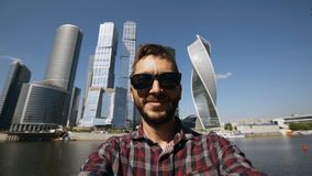 Happy tourist man taking selfie picture using smartphone near international business center in Moscow. Happy tourist man taking selfie picture using smartphone stock video footage