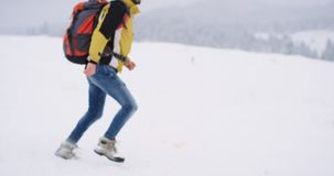 Happy tourist playing with a big white dog in the middle of mountain , he travel in the winter whit his big orange. Tourist bag stock footage