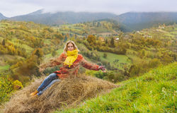 Happy tourist sitting in hay in autumn Royalty Free Stock Images