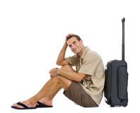 Happy tourist sitting near wheels bag. And dreaming about vacation isolated on white Stock Photo