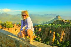Hiking at Desolation Valley. Happy tourist sitting on the rocks after hiking at Valley of Desolation near Graaff-Reinet, South Africa.Sunset light. Blonde woman stock photos