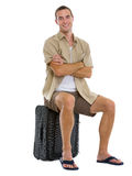 Happy tourist sitting on wheels bag Stock Photo