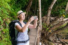 Happy tourist on vacation photographs beautiful landscapes. On the phone Stock Photo