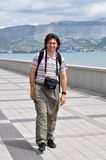 Happy tourist walking on the promenade. Of Novorossiysk on the background of the cargo port Stock Images