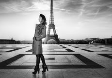 Happy tourist woman against Eiffel tower in Paris, France. Bright in Paris. Full length portrait of happy trendy tourist woman in red coat against Eiffel tower Royalty Free Stock Images