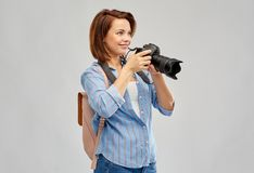 Happy tourist woman with backpack and camera. Travel, tourism and photography concept - happy tourist woman with backpack and camera over grey background royalty free stock images