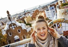Happy tourist woman in Barcelona, Spain sitting on bench. Barcelona signature style. happy young tourist woman in coat in Barcelona, Spain listening audioguide Stock Images