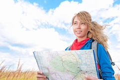 Happy tourist woman with map in summer field. Royalty Free Stock Photo