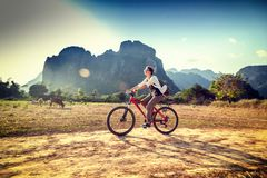 Happy tourist woman riding a bicycle in mountain area in Laos. T. Ravelling in South East Asia stock images