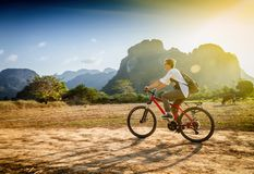 Happy tourist woman riding a bicycle in mountain area in Laos. T Royalty Free Stock Image