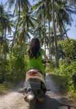 Happy tourist woman riding scooter motorbike in tropical paradise jungle  with blue sky and palm trees in exploring destination an. Back view of young happy Royalty Free Stock Photos