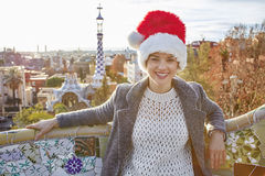 Happy tourist woman in Santa hat at Guell Park sitting on bench Royalty Free Stock Images