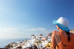 Happy tourist woman on Santorini island, Greece. Travel. Happy woman in sun hat enjoying her holidays on Santorini island, Greece. View on Caldera and Aegean sea Stock Photos