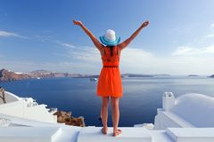 Happy tourist woman on Santorini island, Greece. Travel. Happy woman in sun hat enjoying her holidays on Santorini island, Greece. View on Caldera and Aegean sea Stock Photo