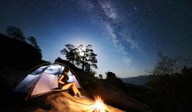 Woman resting beside camp, bonfire and tourist tent at night royalty free stock photos