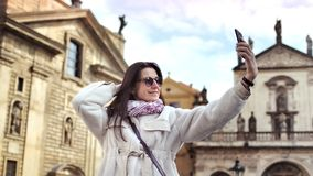 Happy tourist woman smiling taking selfie using smartphone at historic castle background. Adorable elegant travel girl enjoying posing surrounded by medieval stock video