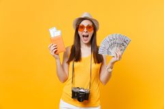 Happy tourist woman in summer casual clothes holding bundle of dollars money, passport isolated on yellow orange royalty free stock photography