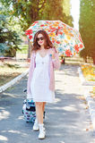 Happy tourist woman in sunglasses and umbrella with suitcase Stock Photos