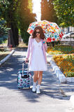 Happy tourist woman in sunglasses and umbrella with suitcase walking in park Stock Photography