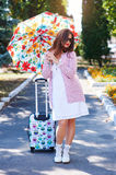 Happy tourist woman in sunglasses and umbrella with suitcase walking in park.  Stock Images
